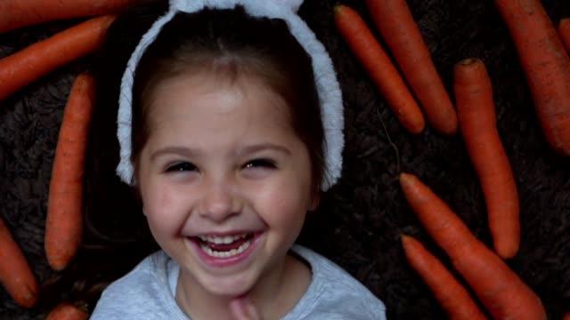 hübsches mädchen lächelt fröhlich beim verlegen in einem feld von karotten - karotte peace stock-videos und b-roll-filmmaterial