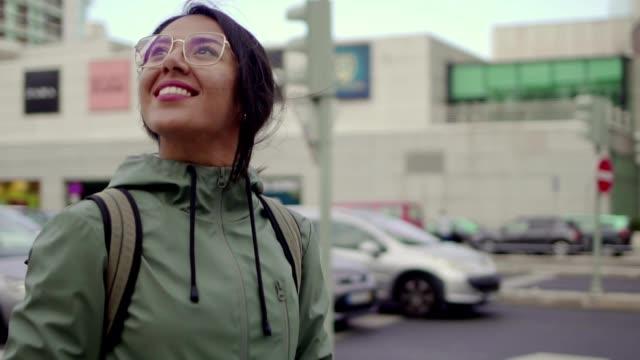 vídeos y material grabado en eventos de stock de niña bonita en el centro de la ciudad mirando a su alrededor sonriendo. - lugar de interés