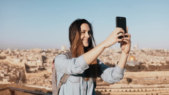 Pretty girl takes selfie in Jerusalem old town. Cute local girl smiles happy, taking photos. Ancient Israel panorama 4K video