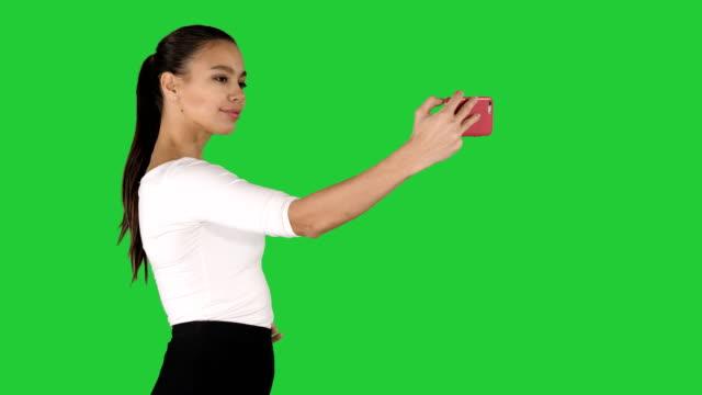 Linda chica tomando un selfie y caminando sobre una pantalla verde Chroma Key - vídeo