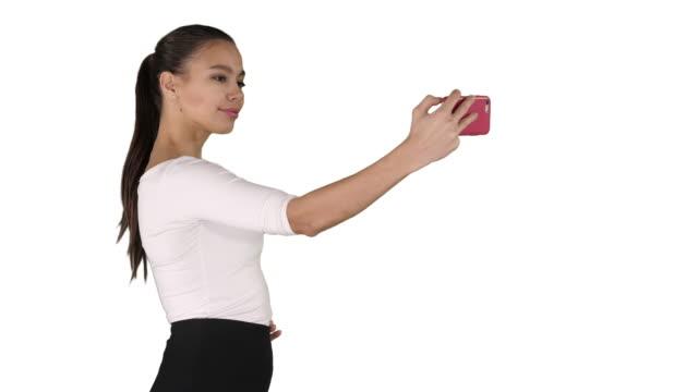 Linda chica tomando un selfie y caminar sobre fondo blanco - vídeo