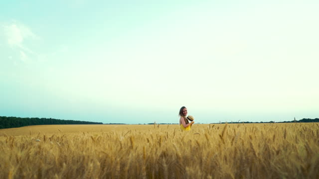hübsches mädchen wirft strohhut im weizenfeld im sommer weg - strohhut stock-videos und b-roll-filmmaterial