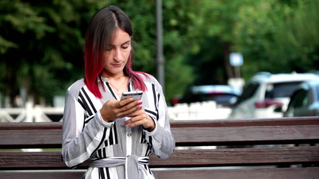 Pretty girl using smartphone in city park, pinc hair video