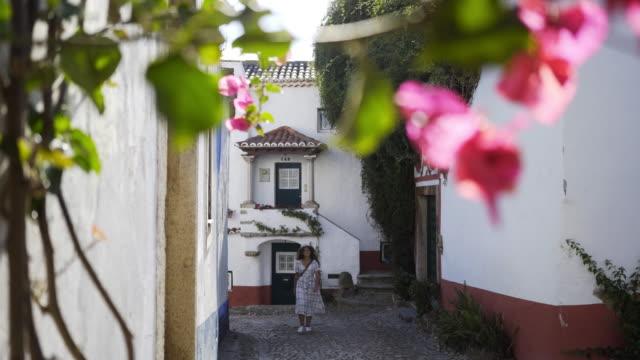 vídeos de stock e filmes b-roll de pretty girl walking on street of historic european town - ivy building