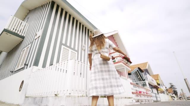 vídeos de stock e filmes b-roll de pretty girl whirling and dancing on street of costa nova - aveiro