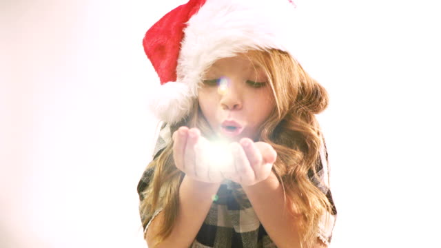 pretty girl with Christmas cap blows golden stars video