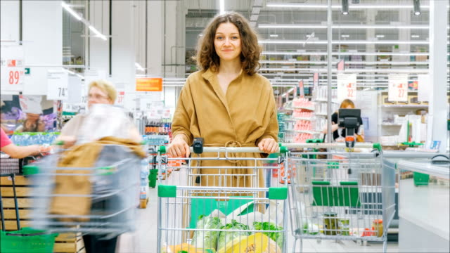pretty girl with loose curly hair stands with shopping cart - vídeo