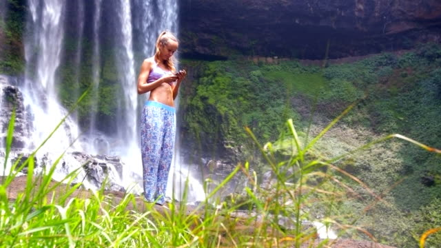 pretty girl with phone stands against waterfall behind grass