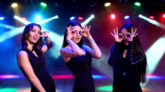Chicas guapas hacen caras divertidas en una fiesta en la oscuridad. - vídeo