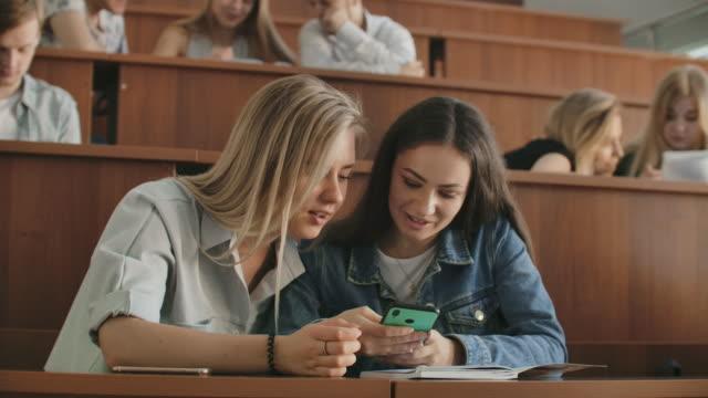 hübsche mädchen studenten sind mit demsmartphone, beobachten des bildschirms, reden und lachen sitzen an den tischen an der universität. social media, internet, millennials und bildungskonzept. - vorlesungsfrei stock-videos und b-roll-filmmaterial