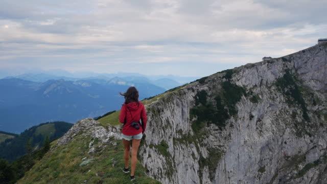 vídeos de stock, filmes e b-roll de garota bonita caminhando no pico da montanha schafberg em salzkammergut áustria. jovem mulher sexy de jaqueta vermelha com câmera subindo em cenário alpino. - áustria