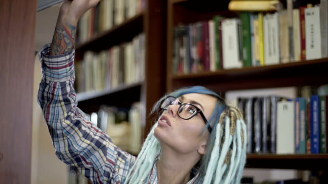 Pretty hipster woman in glasses with dreadlocks choosing book for reading on leisure time at college library Portrait of a hipster woman reading book in library blue hair stock videos & royalty-free footage