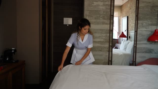 pretty house keeper working at a hotel making a bed - addetto alle pulizie video stock e b–roll