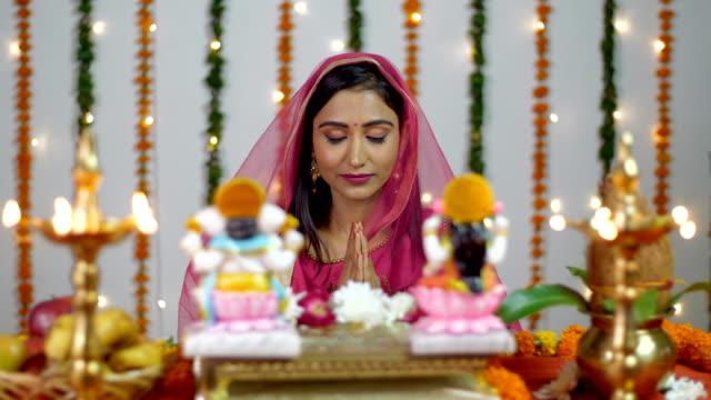 pretty indian female praying in front of hindu gods lakshmi and ganesh on diwali - hinduizm filmów i materiałów b-roll