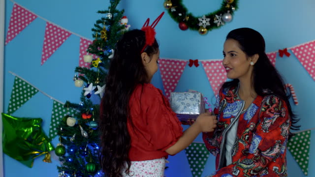 Pretty Indian mother gifting her daughter a colorful present on Christmas Eve Cute little girl getting a special gift box from her beautiful mom with decorated Christmas tree in the background - Christmas surprise indian family stock videos & royalty-free footage
