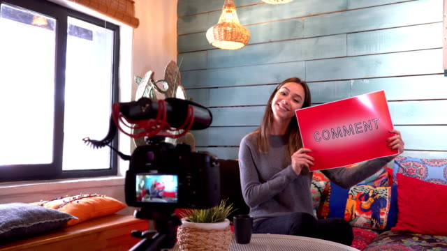 Pretty influencer is showing ''comment'' word with cardboard