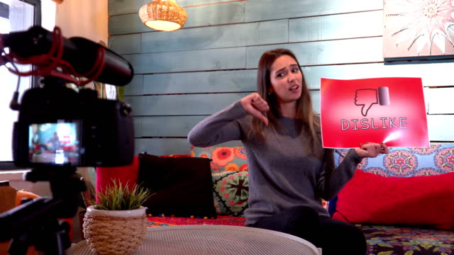 Pretty influencer is showing ''dislike''sign with cardboard