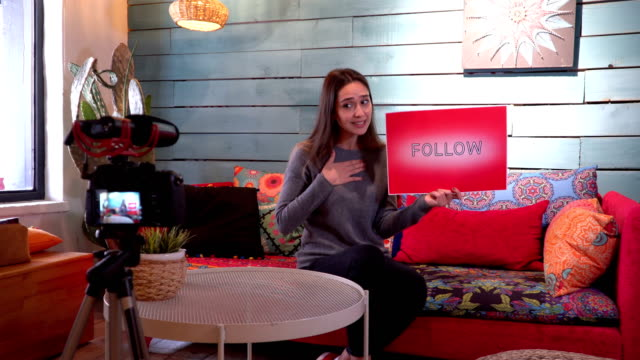 Pretty influencer is showing ''follow'' word with cardboard