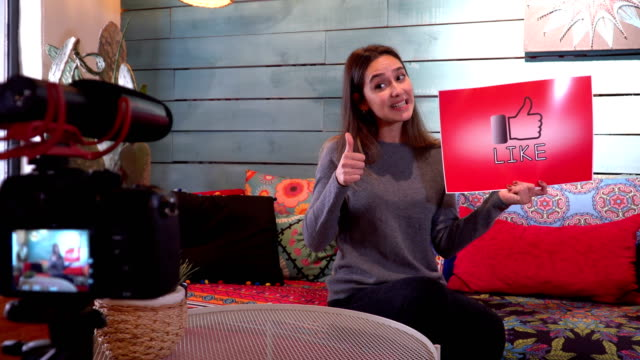 Pretty influencer is showing ''like''sign with cardboard
