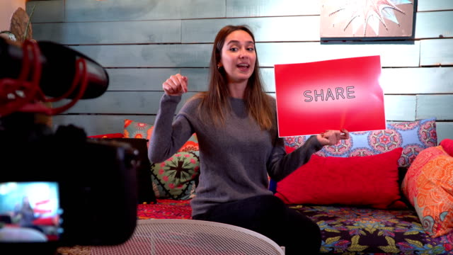Pretty influencer is showing ''share'' word with cardboard