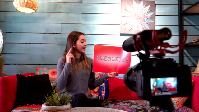Pretty influencer is showing ''subscribe'' word with cardboard