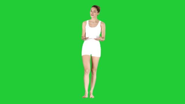 vidéos et rushes de jolie moniteur expliquant et décrivant la façon de faire des exercices avant l'entraînement sur un écran vert, chroma key - homme slip