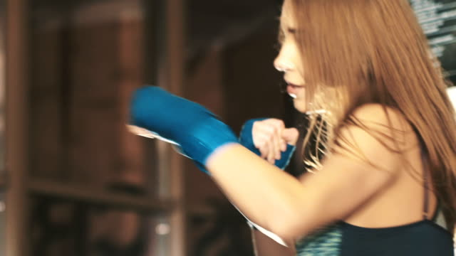 Pretty kickboxing girl training with punching bag in a fitness gym. Slowly video