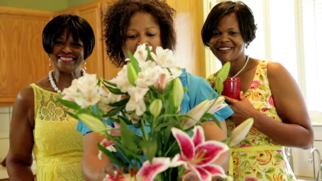Pretty ladies arranging flowers and smile at camera