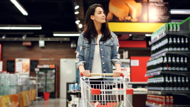 Pretty lady in casual clothes is walking in grocery store steering shopping trolley with food inside it and looking around at shelves with products. Women and shops concept. Pretty young lady in casual clothes is walking in grocery store steering shopping trolley with food inside it and looking around at shelves with products. Women and shops concept. woman pushing cart stock videos & royalty-free footage