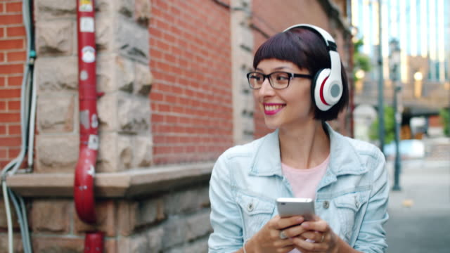 Pretty lady listening to music in headphone using smartphone walking in street Slow motion of pretty lady listening to music in headphone using smartphone walking outside in street having fun. People, devices and urban lifestyle concept. bluetooth stock videos & royalty-free footage