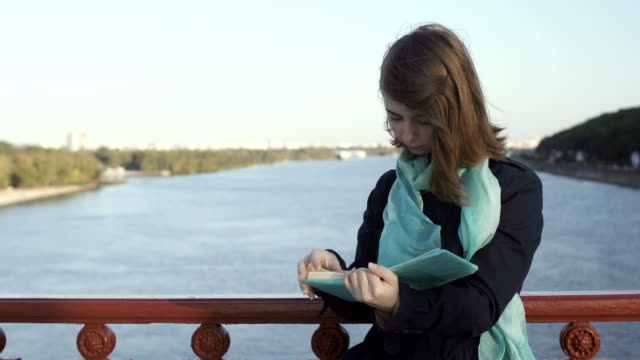 Pretty lady reads the book at the bridge video