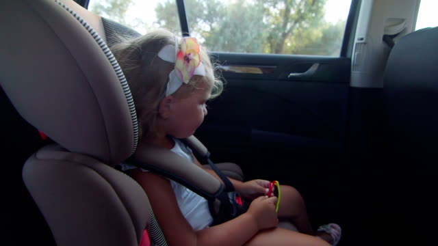 urocza dziewczynka śpiewa piosenki z dziecko siedzi w siedzeniu samochodu na wycieczkę - mebel do siedzenia filmów i materiałów b-roll