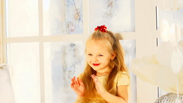 Pretty little girl sits on a windowsill and praying video