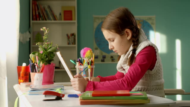 pretty little school kid wants to do homework on the tablet at the table at home on sunny day - primary school stock videos and b-roll footage