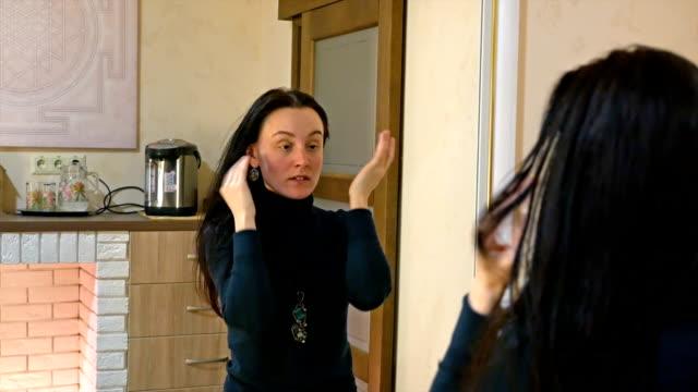 Pretty long hair woman applies cream on her face video