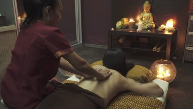 pretty masseuse does a back massage to girl - alternative medicine stock videos and b-roll footage