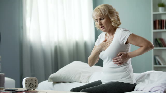 Pretty mature woman sitting on bed and suffering from heart attack, health video