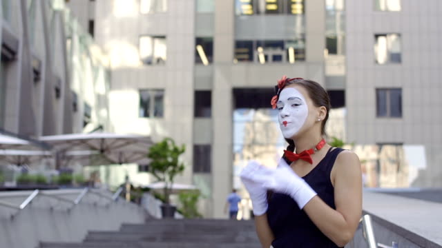 Pretty mime girl playing her role at office center background Young girl mime show her emotions on camera. Portrait of funny comic playing with facial expressions and gesticulating hands. greasepaint stock videos & royalty-free footage