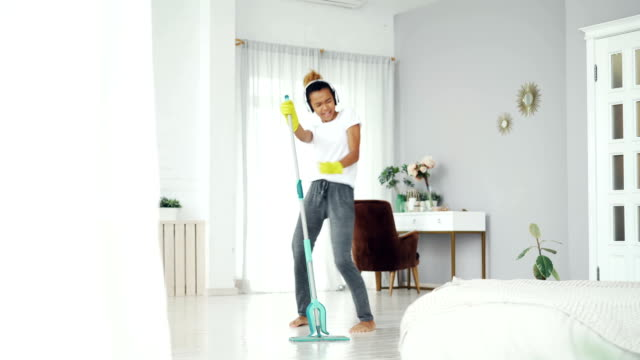 Pretty mixed race girl cheerful maid is cleaning floor in beautiful flat with plastic mop and listening to music, singing and dancing. Routine and fun concept. Pretty mixed race girl cheerful maid is cleaning floor in beautiful flat with plastic mop and listening to music, singing and dancing. Routine, house and fun concept. cleaning stock videos & royalty-free footage
