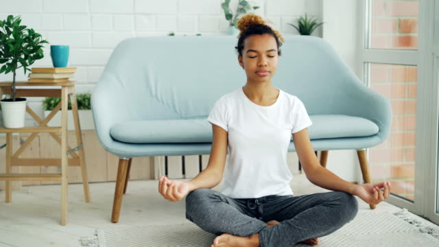Pretty mixed race girl is sitting on floor in lotus position with hands on knees and meditating, enjoying relaxation and tranquility. Yoga, people and home concept. Pretty mixed race girl is sitting on floor in lotus position with hands on knees and meditating, enjoying relaxation and tranquility. Yoga, young people and home concept. eyes closed videos stock videos & royalty-free footage