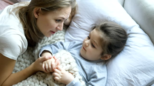 pretty mother tells fairy tale to daughter under blanket - vídeo