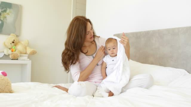 pretty mother trying to wrap up cute baby daughter - cosy pillows mother child bildbanksvideor och videomaterial från bakom kulisserna