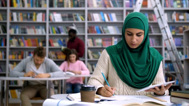 pretty muslim female student learning in library - abbigliamento religioso video stock e b–roll