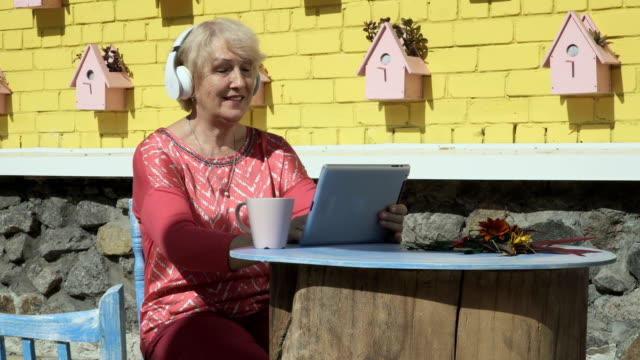 Pretty old woman listens music and uses tablet video