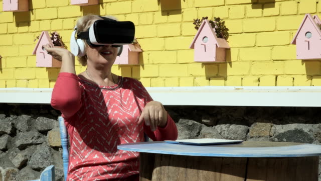 Pretty old woman uses virtual reality glasses video
