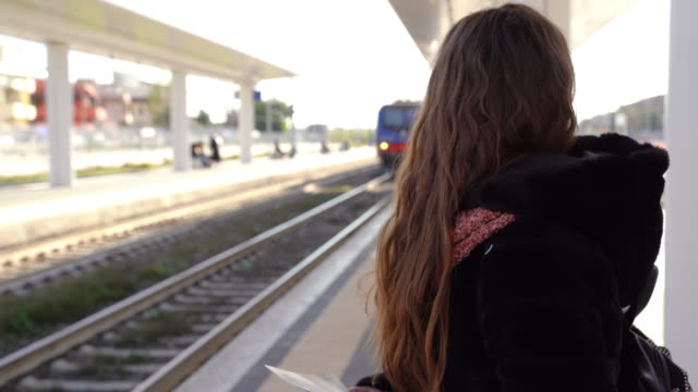 pretty red hair girl with red lips standing at the station platform with tickets and smiling on camera while train arriving. female passenger waiting for public commuter at the urban station, trip by train and travel destination - parapetto barriera video stock e b–roll