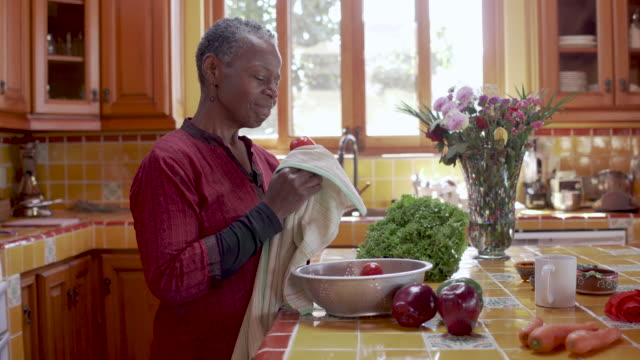 Pretty retired black woman washing her vegetables in her kitchen