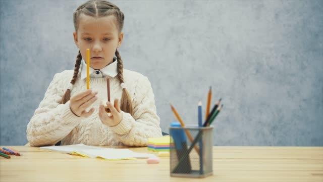vídeos de stock, filmes e b-roll de o aluno bonito encontra difícil afiar seu lápis marrom. - afiado