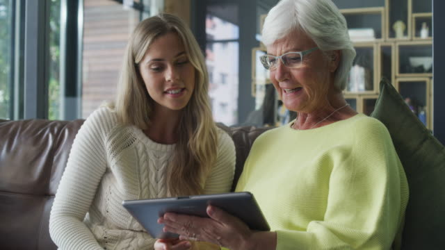 Pretty simple, isn't it? 4k video footage of a young woman and her elderly relative using a digital tablet together at home surfing the net stock videos & royalty-free footage