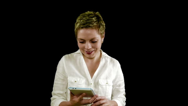 Pretty smiling blond woman texting by tablet pad video